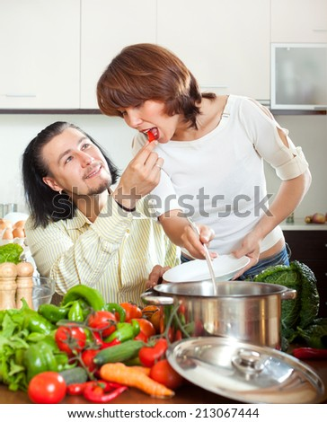 Brunette beautiful housewife with man cooking with fresh vegetables at home kitchen