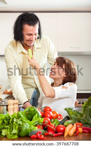 Brunette beautiful housewife with man cooking with fresh vegetables at home kitchen - stock photo