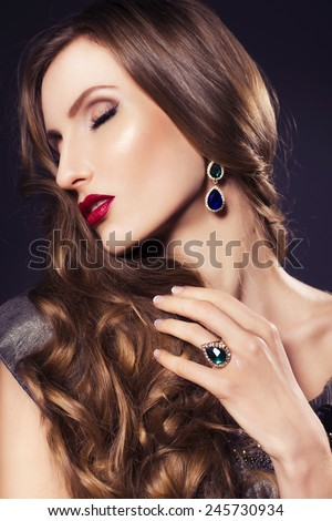 Brunette beautiful luxury woman in dress with clear skin and evening dark make up: green cat eye and brown eyeshadows. Waved hairstyle. Dark background