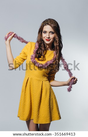 Brunette beautiful smiling girl wearing yellow dress standing on white isolated background. Party concept