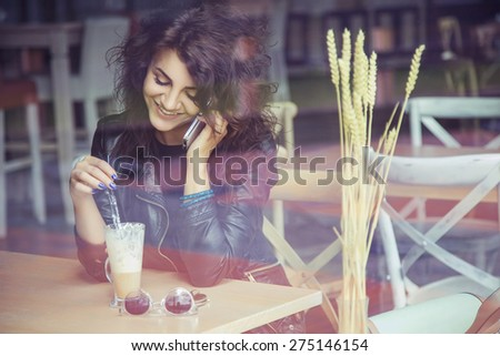 Brunette beautiful stylish caucasian woman in casual outfit on a walk on european city street sitting at the cafe talking on her phone. copy space - stock photo