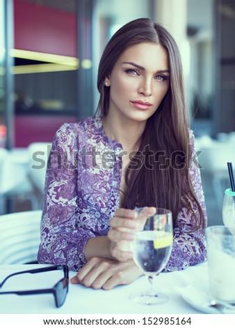 Brunette beauty drinking water in restaurant - stock photo