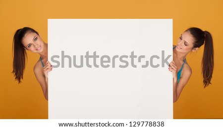 brunette bikini girl holding a white blank board - stock photo