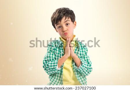 Brunette boy pleading over ocher background  - stock photo