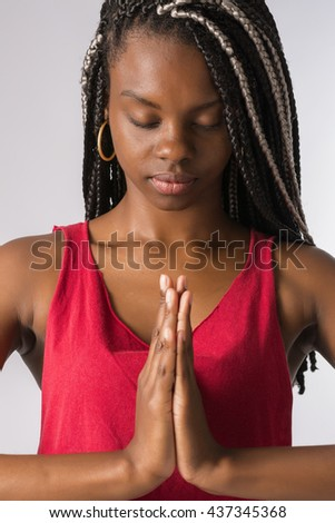 Brunette Brazilian woman, afro descendant, with long and braided hair, meditating with hands together in prayer and closed eyes. - stock photo