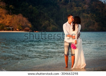 brunette bride and handsome groom barefoot walk at sand beach at dawn