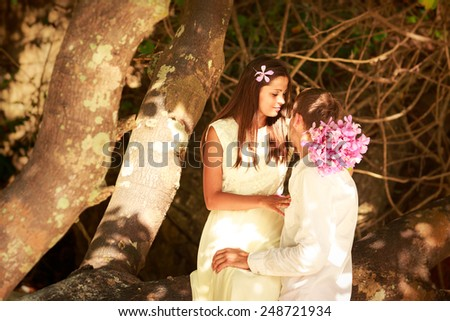 brunette bride in long white wedding dress sitting on the big tree and hold her handsome groom on island beach in Thailand - stock photo