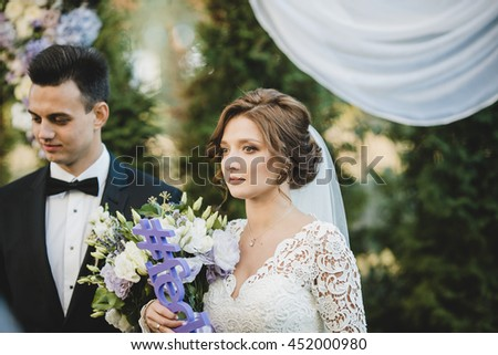 Brunette bride looks seriously standing under the wedding altar with lots of bouquets