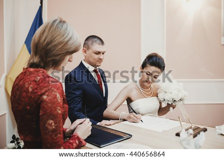 Brunette bride signs papers about engagement