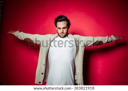 Brunette brown haired man with beard and white t-shirt and grey hoody in front of red studio backdrop - stock photo