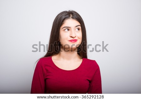brunette business woman lost in thought, in a red dress, studio isolated portrait emotions
