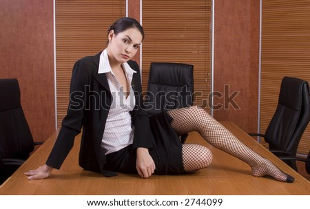 Brunette business woman with black suit on boardroom table