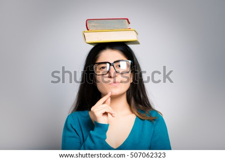 brunette businesswoman holding books on her head, close-up isolated on a gray background