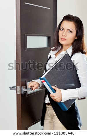 brunette businesswoman holding file and opening the dark brown door - stock photo