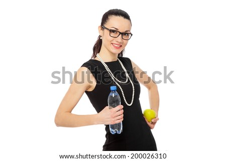 brunette businesswoman in black dress holding apple and bottle of water over white background. healthy lifestyle