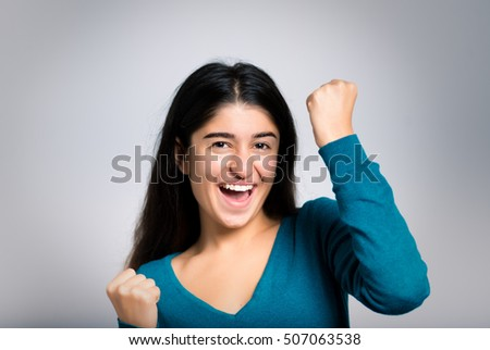 Brunette businesswoman rejoicing with fists, close-up isolated on a gray background