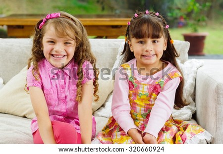 Brunette children sisters sitting happily on white livingroom sofa posing for camera with typical pink girl clothes. - stock photo