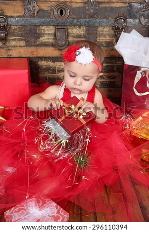 Brunette christmas baby wearing a red dress - stock photo