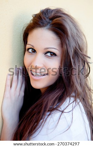 Brunette cool girl with brackets resting on a yellow wall