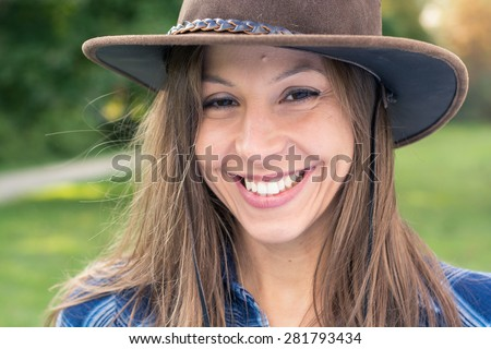 Brunette cowgirl smiling - stock photo