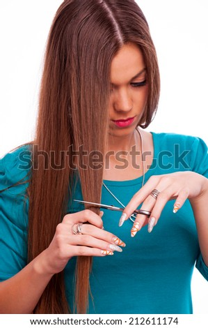 Brunette cutting her own hair, isolated on white  - stock photo