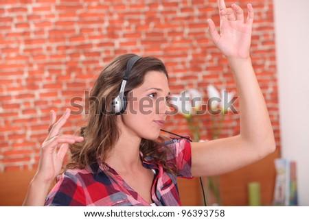 Brunette dancing wearing headphones - stock photo