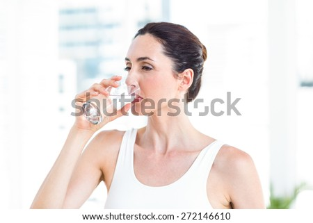 Brunette drinking water in the living room - stock photo