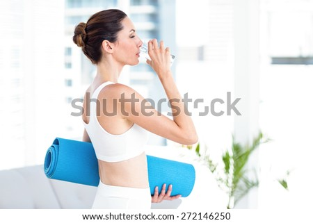 Brunette drinking water while holding exercise mat in the living room - stock photo