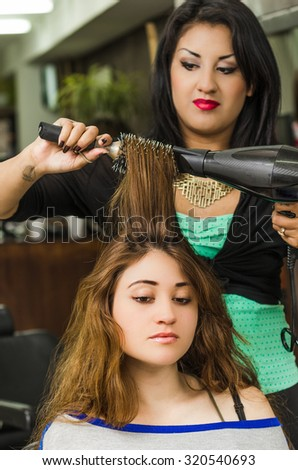 Brunette facing camera getting hair done by professional stylist.