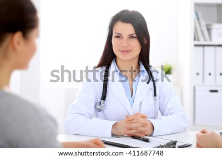 Brunette female doctor talking to patient in the hospital - stock photo