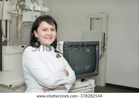 Brunette female doctor working with x-ray machine - stock photo