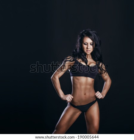 brunette female fitness model with perfect body posing on black background  - stock photo