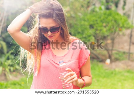 Brunette female model in outdoors park environment posing holding her hair and bottle of water - stock photo