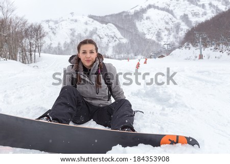Brunette female snowboarder with braids  is seated on the fresh snowy ground, close to the ski lift, while she looks, with happiness, the camera. - stock photo