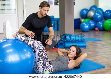 Brunette female working out at a gym with personal trainer - stock photo