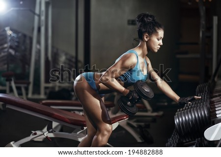 Brunette fitness girl lifting dumbbell. Fitness woman performing back exercises with dumbbells - stock photo