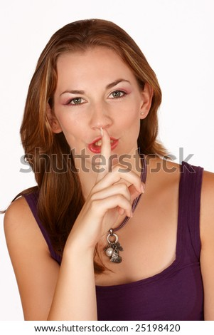 Brunette gesturing for silence with finger on lips