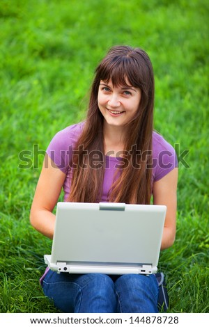 Brunette girl at green grass with notebook