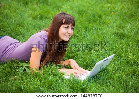 Brunette girl at green grass with notebook - stock photo