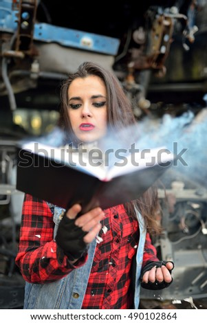 brunette girl blowing flames of a book