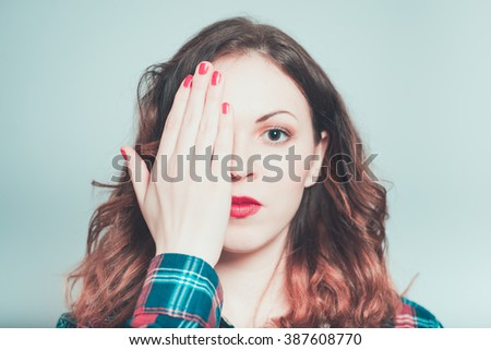 brunette girl closed her eyes with her hands on a white grey - stock photo