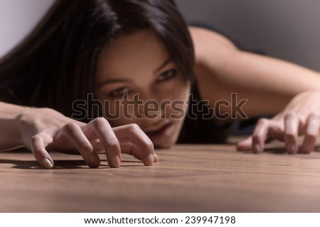 brunette girl crawling on floor and looking into camera. crazy and doped woman demon possessed like zombie on floor - stock photo