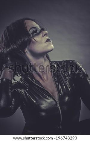 brunette girl dressed in black latex jumpsuit - stock photo