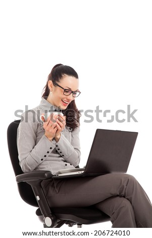 brunette girl drinking coffee, sitting in the chair with laptop over white background