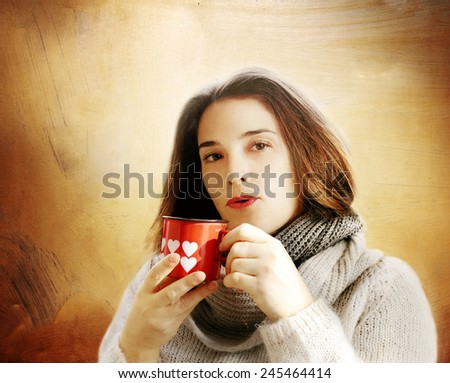 brunette girl drinking hot beverage  inside funny glass with hearts against golden background - stock photo