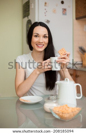 brunette girl drinking tea with cookie in the morning in the kitchen   - stock photo
