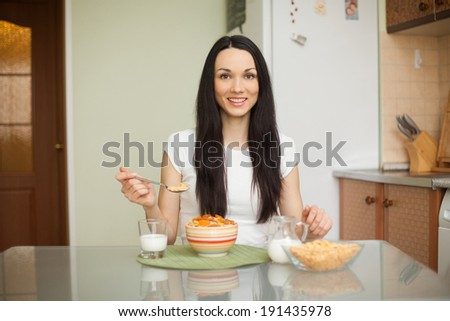 brunette girl eating breakfast with milk in the kitchen  - stock photo