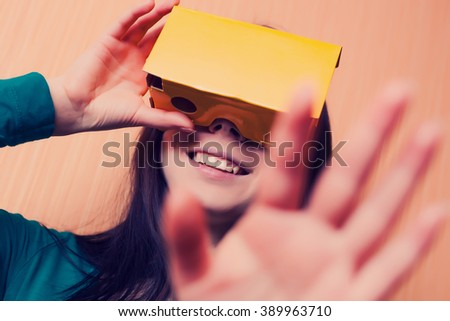 Brunette girl having fun playing with her cardboard virtual reality headset attached to her smart phone. Modern technology and vintage hipster colors  - stock photo