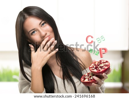 Brunette girl holding a Pomegranate in kuhne. 3d vitamins - stock photo