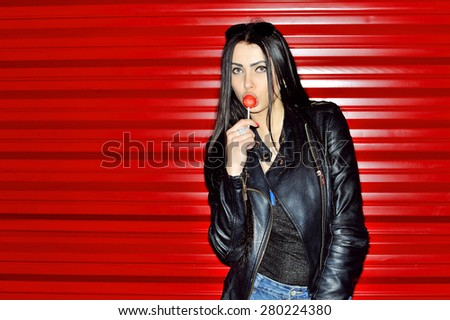 Brunette girl holding and licking round red sugar candy standing on red wall. Copy space - stock photo